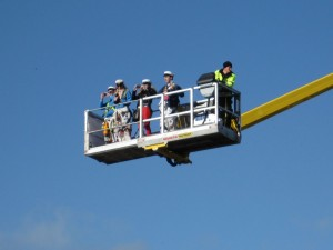 A few people in a skylift high up above the crowds.