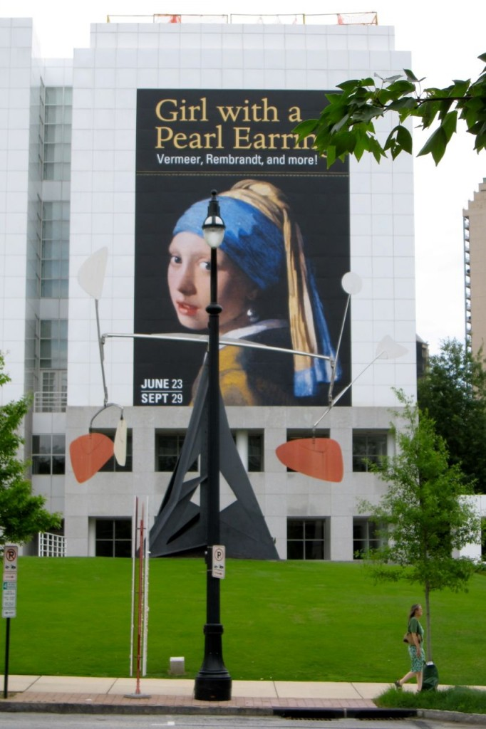 """A poster on the wall of the Museum building advertising a coming exhibition of Dutch masters  (F.ex. Johannes Vermeer Dutch 1632-1675 or Rembrandt Harmenszoon van Rijn, Dutch 1606-1669) """"Dutch Paintings from the Mauritshuis"""" June 23 - September 29 2013. In the front is a sculpture by Alexander Calder (American 1898 - 1976) """"Three Up, Three Down"""" from 1973."""