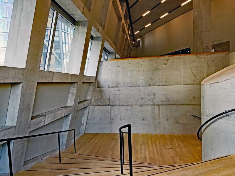 The nice sweeping lines of the staircase in contrast to the angular elements in the structure. Also note the contrast between the harsher concrete and the warm wood flooring.