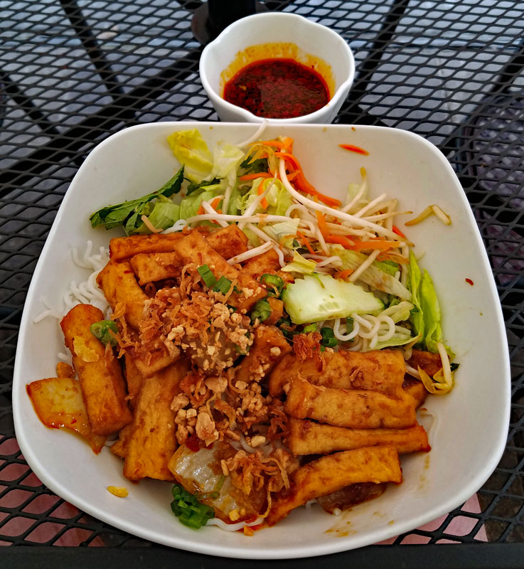 VERMICELLI BOWL– BÚN - LEMONGRASS TOFU – TÀU HỦ XÀO XẢ ỚT includes lettuce, mint, bean sprouts, cucumber, scallion, oil, roasted onions, peanuts, fish sauce and vinaigrette. This is a clear favorite, exceptionally tasty and who can possibly miss meat with tofu this good? Such a pleasure for your palate!