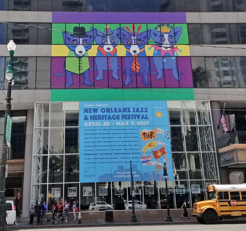 Ad for this years Jazzfest outside the Sheraton on Canal Street with George Rodrigue's Loup Garou on top