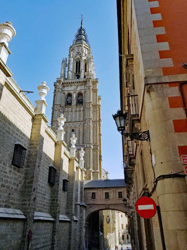 """A view down a Toledo street with tower and parts of """"The Primate Cathedral of Saint Mary of Toledo"""" visible."""