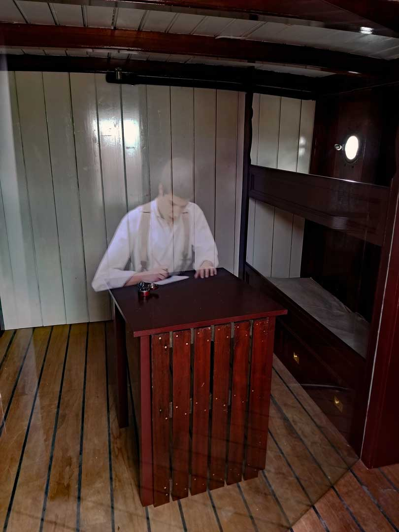 An image from a cabin with a hologram of a young sailor writing a letter, to home maybe...
