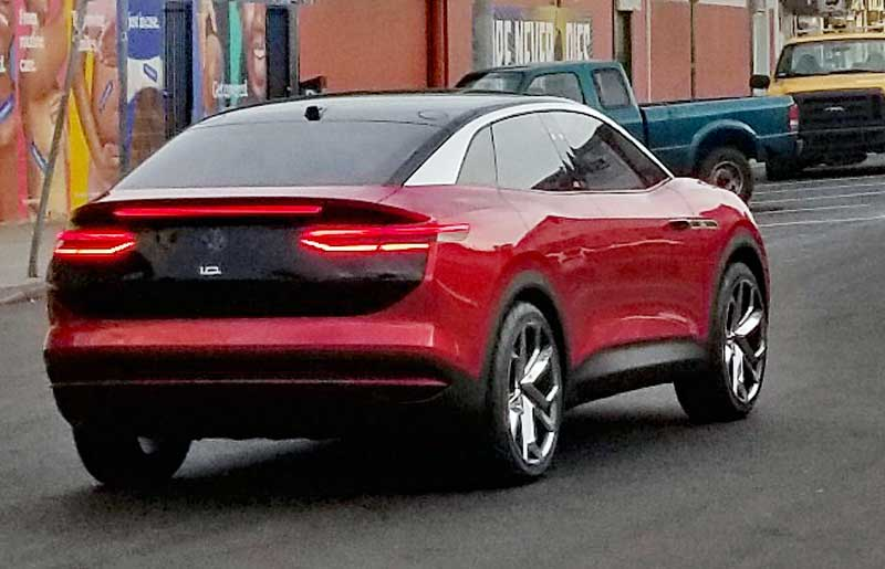 A Red sedan that is assumed to be another new VW seen closer