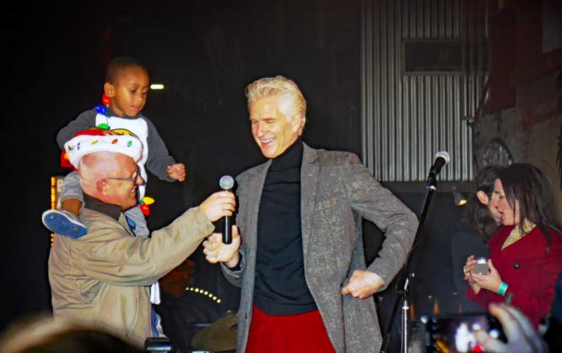 Councilman Mike boning hands the microphone to local actor Matthew Modine for the sign lighting ceremony