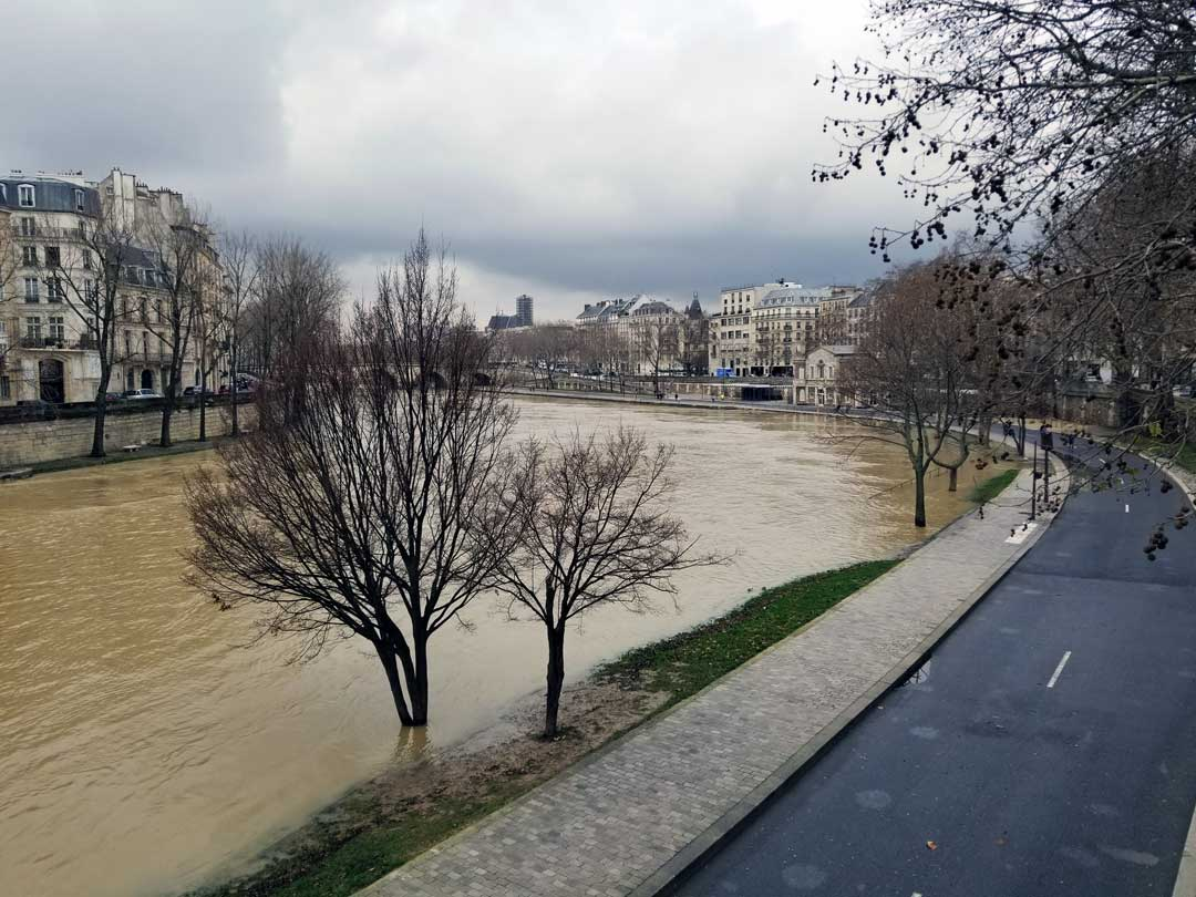 Looking out over the river Seine with Ice St-louis in the background, notice the trees underwater in the foreground, that is normally a parklike area with a walkway.