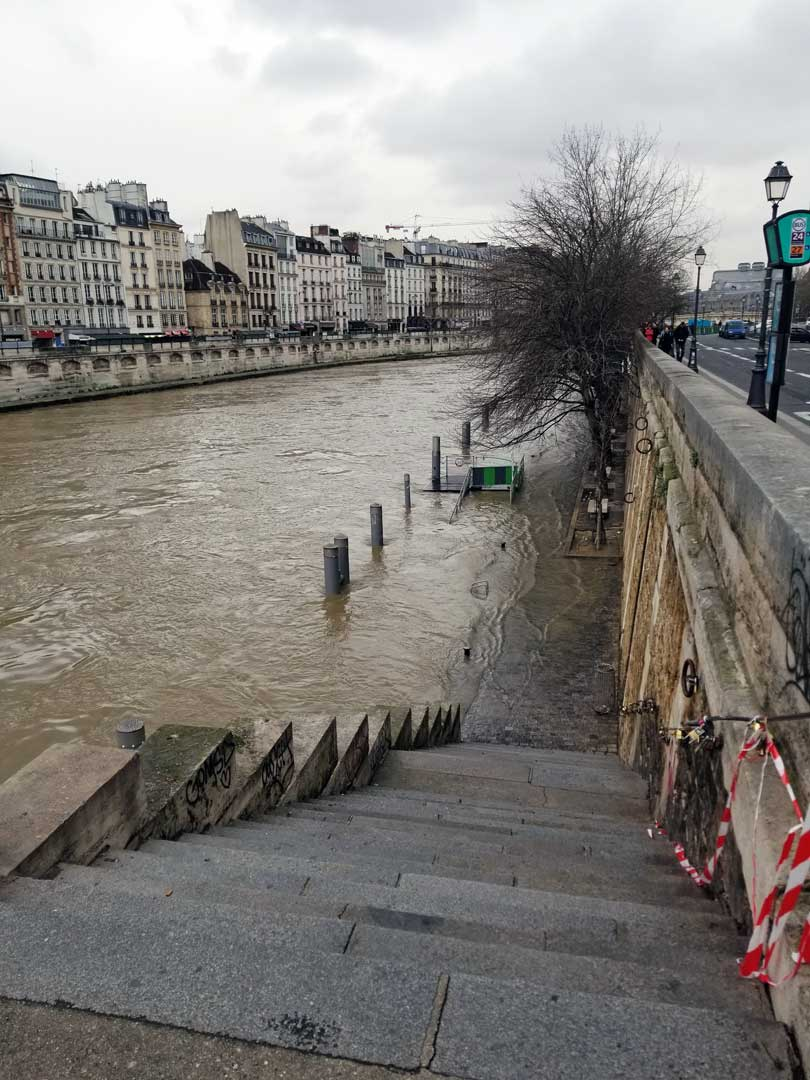 Flooded stairs leading down to a walkway by the Seine.