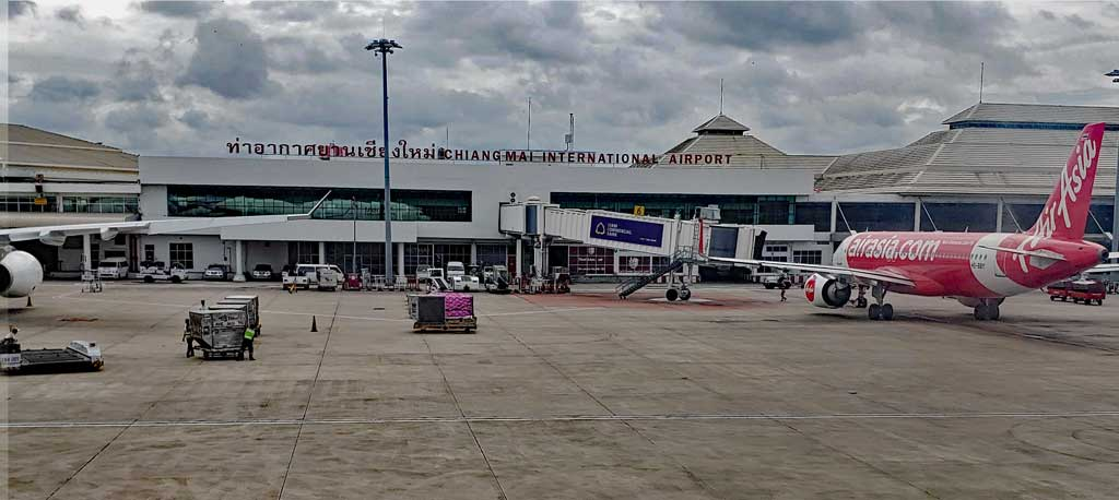 Chiang Mai airport designation - CNX - with the terminal building as seen from the tarmac.