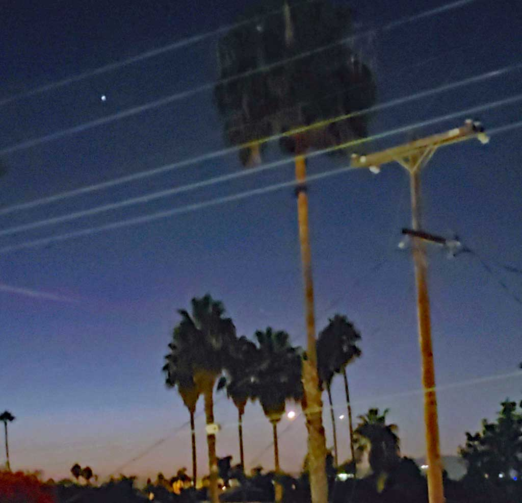 The bright light between the palm trees to the left is the rocket.
