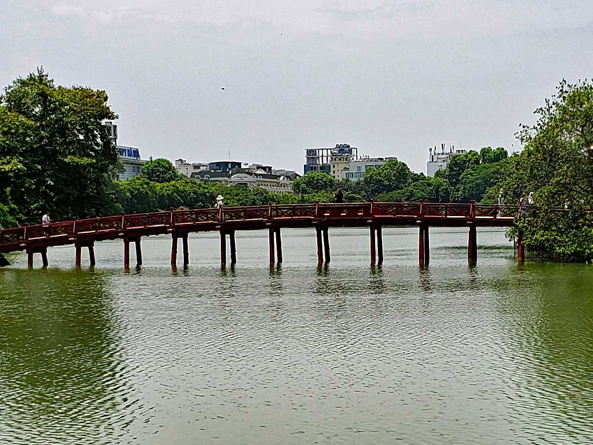 "The ""Morning sunlight bridge"" leading  to the ""Jade islet"" in the ""Hoàn Kiếm Lake"" where the ""Temple of the Jade Mountain"" is located."