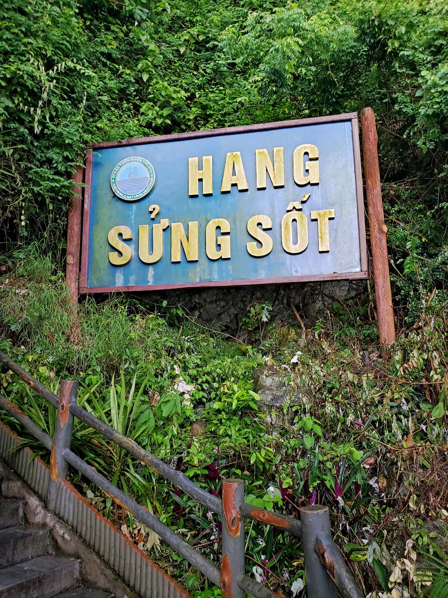 Hang Sung Sot cave sign by the steep staircase leading up to the entrance of the cave.