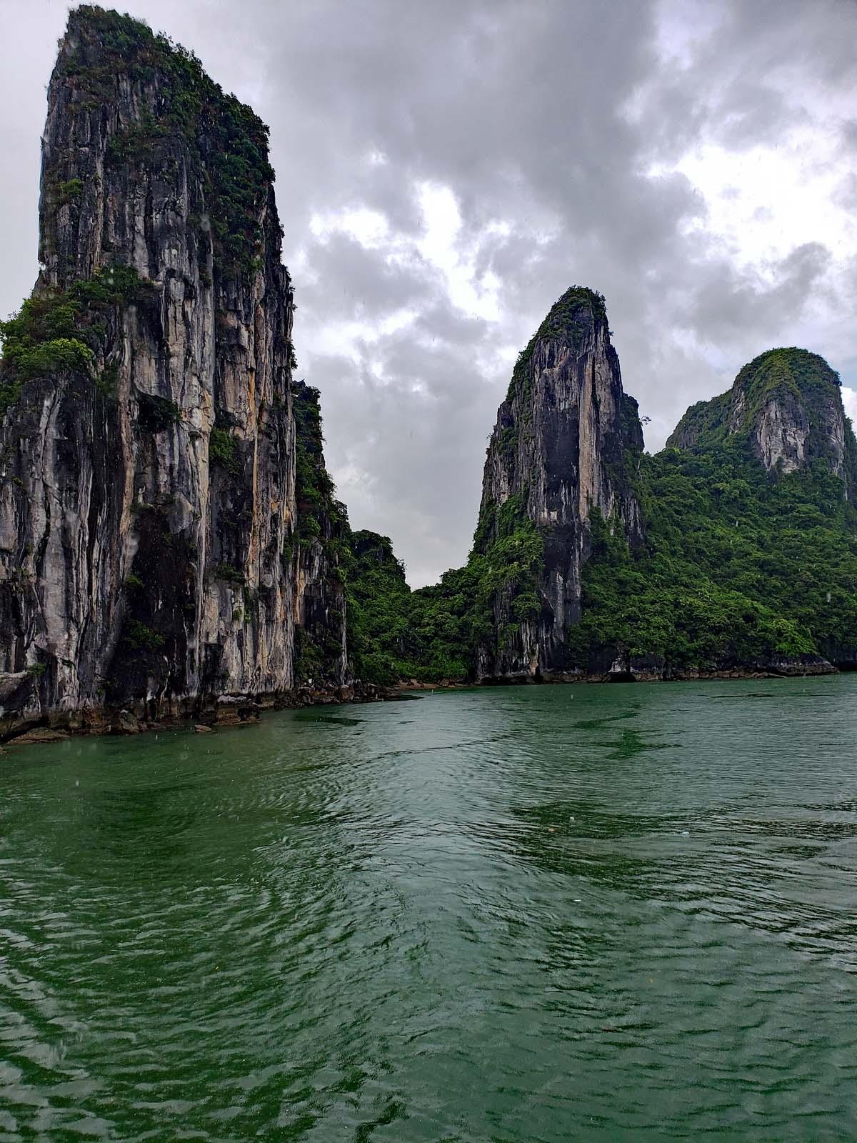 More limestone cliffs against dark rain filled clouds.