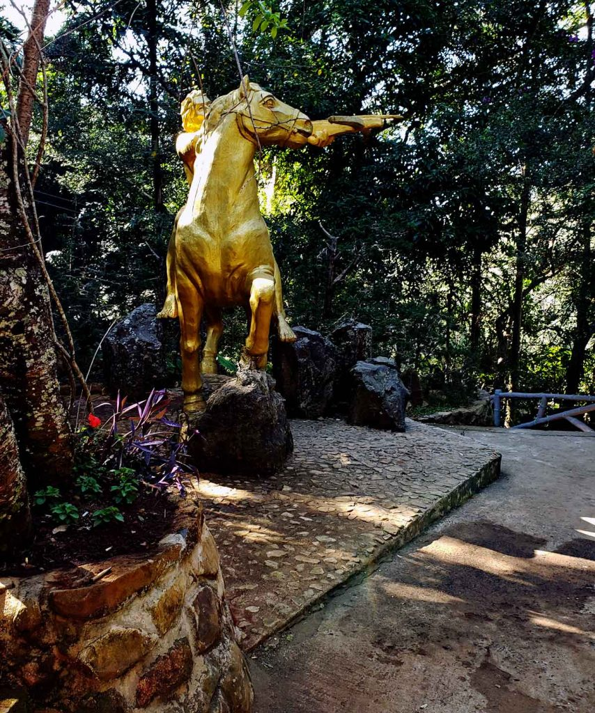 A statue of a golden warrior with a cross bow.