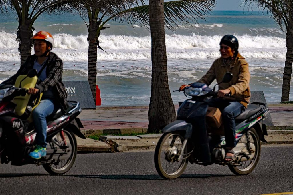 Scooters riding along the beach road.